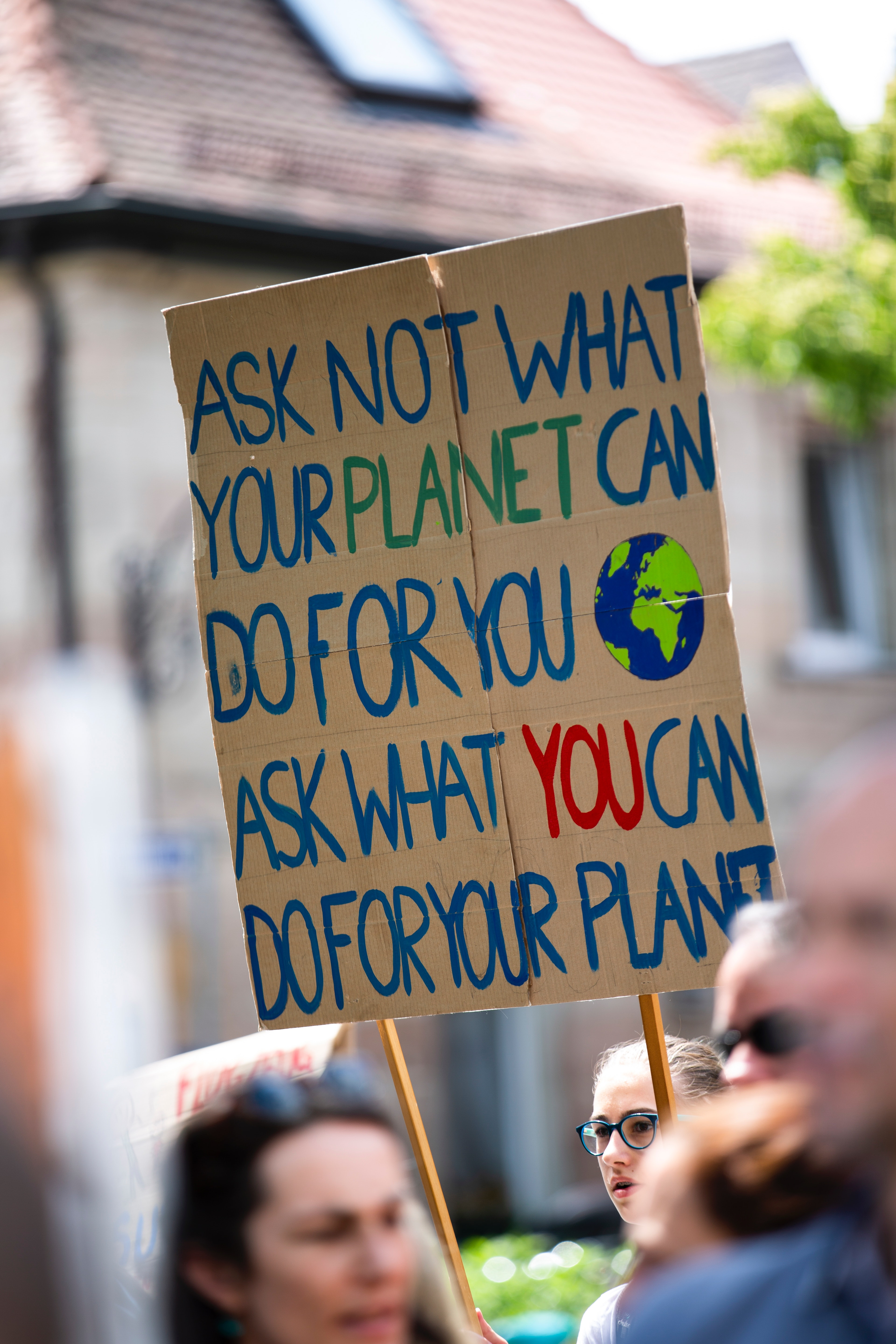 A remote worker environmental protester with a placard asking us what we can do to help save the planet and solve climate change.