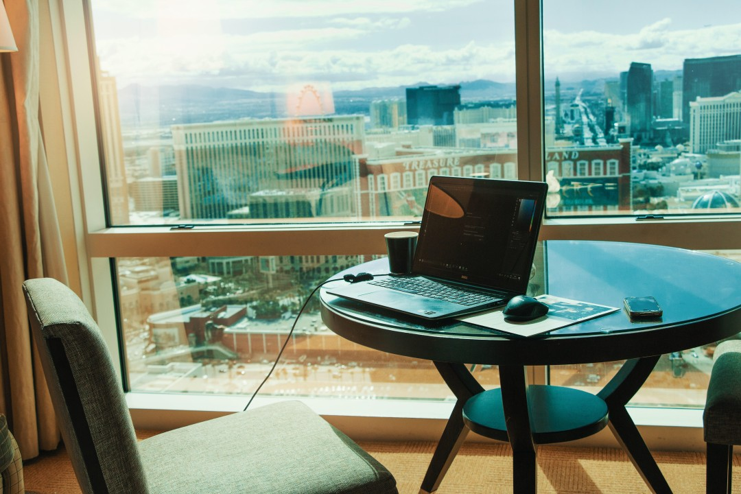 A remote working set up from a third workplace like a cafe, coffee shop, hotel lobby, hotel room or even a library thanks to the perks of flexible working and hybrid working
