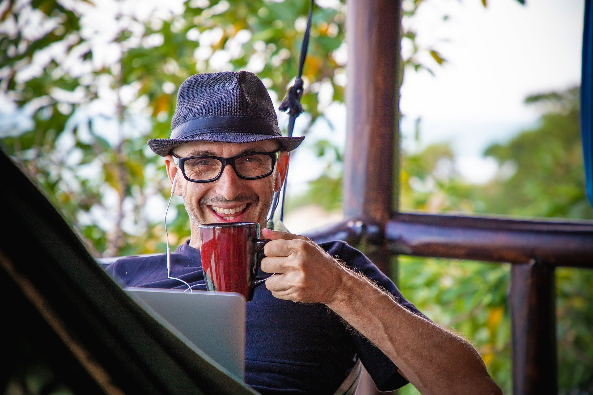 A remote worker drink coffee and smiling because he has the freedom of working together from anywhere thanks to Wurkr